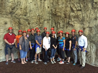 Fenton Area Public Schools Admin Team Pose in Front of a Rock Climbing Wall